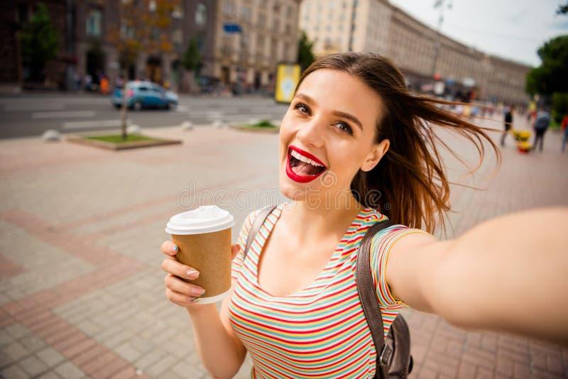 Zamyka w górę fotografii radosna dziewczyna z skwaśniałym imbirowym włosianym czerwonym warga kijem robi fotografii mienia za kub obrazy royalty free
