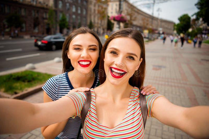 Zamyka w górę fotografii rozochocone damy jest ubranym pasiastą koszulkę w mieście outdoors z czerwonym warga kijem robi fotograf zdjęcie royalty free