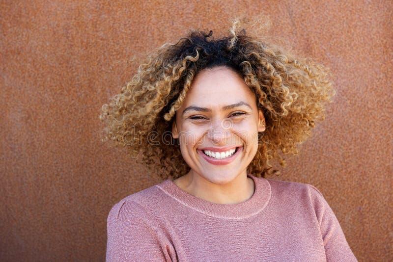Zamyka w górę horyzontalnej pięknej amerykanin afrykańskiego pochodzenia kobiety ono uśmiecha się przeciw brązu tłu obraz royalty free