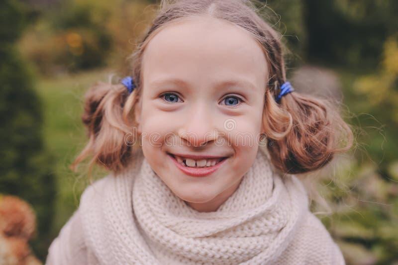 Zamyka w górę jesień szczerego portreta śliczna szczęśliwa dzieciak dziewczyna w ciepłym trykotowym pulowerze obraz stock