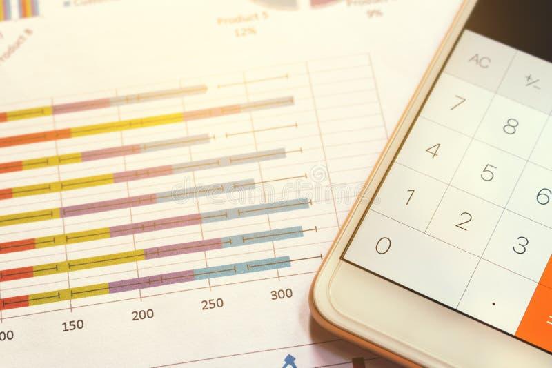 Zamyka w górę kalkulatora w smartphone i zbiorczego raportu na stołowym biurze obrazy royalty free