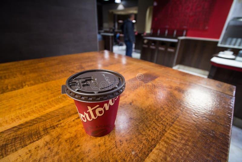 Zamyka w górę kartonowej filiżanki z Tim Hortons logo w jeden ich restauracje w Montreal dalej, Quebec obrazy stock