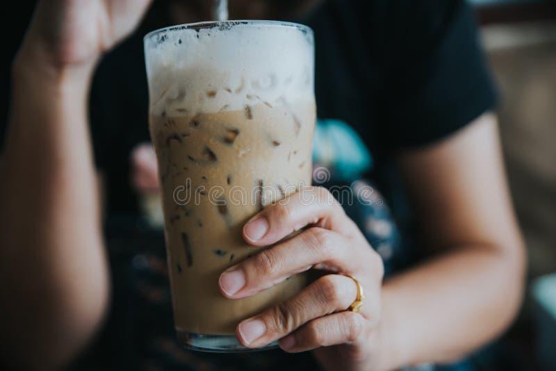 Zamyka w górę kobiety pije kawę przy sklep z kawą obraz royalty free