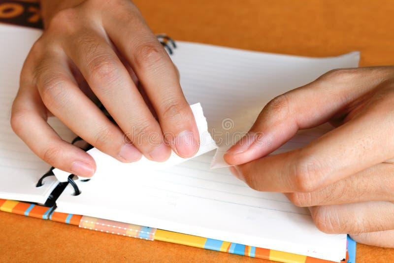 Zamyka w górę kobiety ręki rozdziera lub drzeje białego papier przy notatnikiem zdjęcia stock