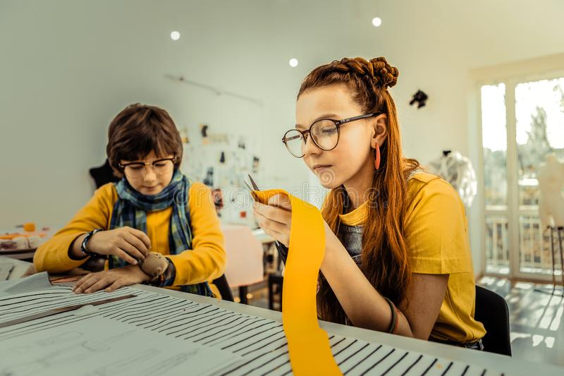 Zamyka w górę kreatywnie dziewczyny tnącego żółtego faborku w projekt szkole zdjęcia royalty free