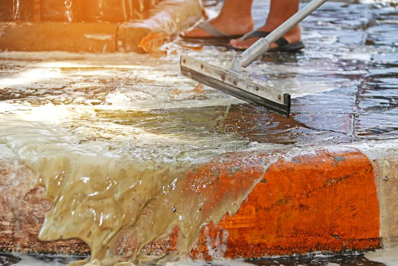 Zamyka w górę kwacza pracownika czyści brudnego footpath fotografia royalty free