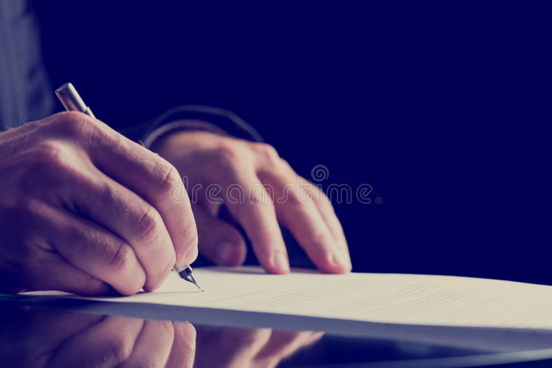 Zamyka w górę Ludzkiego ręki podpisywania na Formalnym papierze zdjęcie royalty free