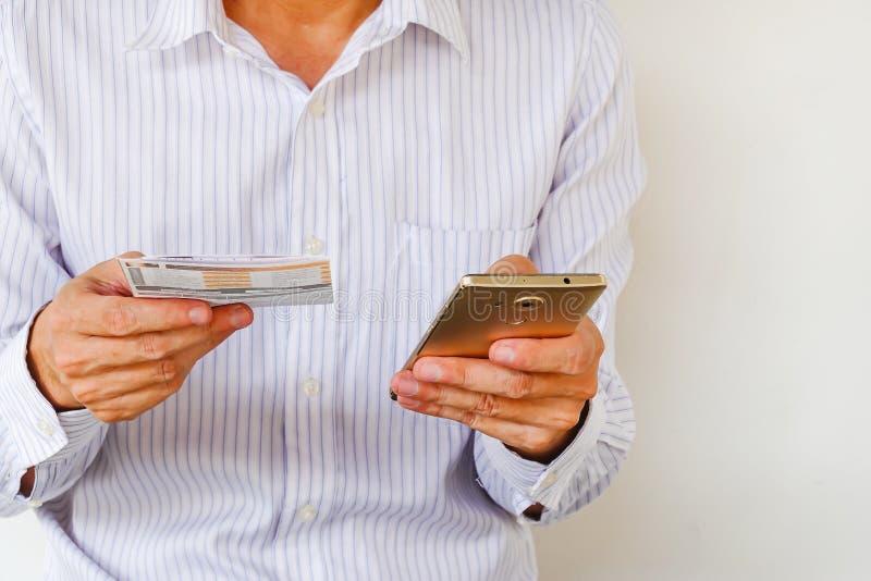 Zamyka w górę mężczyzna listy kontrolnej używać bankowość dla karty kredytowej telefonem komórkowym z rachunkami w minis obraz royalty free