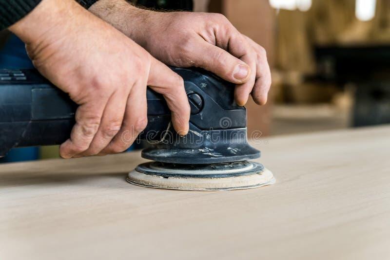 Zamyka w górę mężczyzna sanding drewna w warsztacie zdjęcie royalty free
