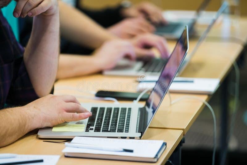Zamyka w górę mężczyzny pracuje na laptopie podczas biznesowej konferencji zdjęcia royalty free