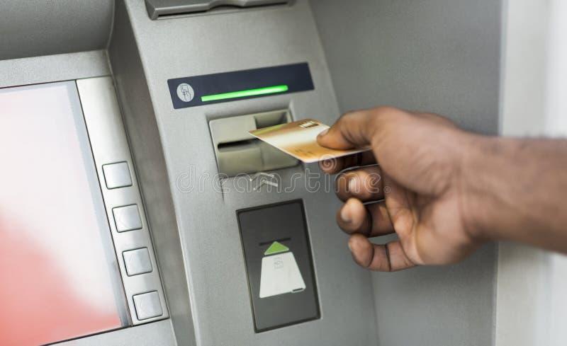 Zamyka w górę mężczyzny używa ATM z złocistą kartą kredytową zdjęcie stock