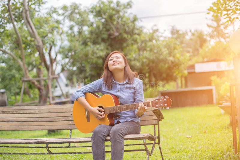 Zamyka w górę młoda kobieta ćwiczyć modniś gitary w parku i cieszy się, szczęśliwy bawić się gitarę obrazy royalty free