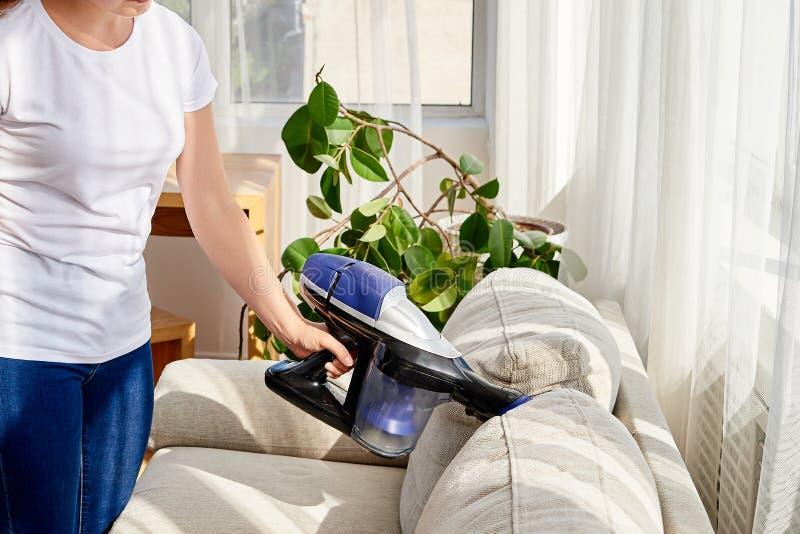 Zamyka w górę młodej kobiety w białej koszula i cajgach czyści kanapę z próżniowy czystym w domu, kopii przestrzeń household obrazy stock