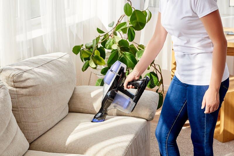 Zamyka w górę młodej kobiety w białej koszula i cajgach czyści kanapę z próżniowy czystym w domu, kopii przestrzeń household obraz stock