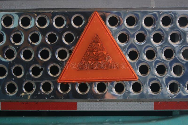 Zamyka w górę metal błyszczącej siatki z pomarańczowym światłem odbija ostrzegawczego trójboka i białą linię zdjęcie stock