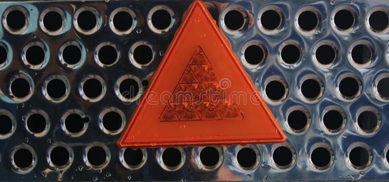Zamyka w górę metal błyszczącej siatki z pomarańczowym światłem odbija ostrzegawczego trójboka obraz stock