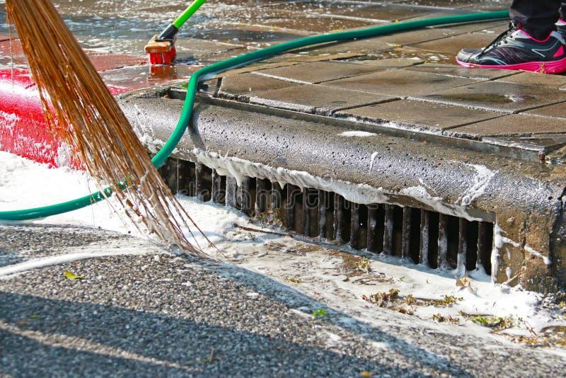 Zamyka w górę miotła pracownika czyści brudnego footpath obrazy stock