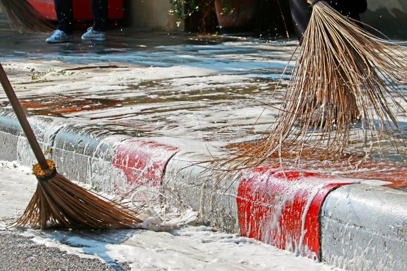 Zamyka w górę miotła pracownika czyści brudnego footpath obraz royalty free