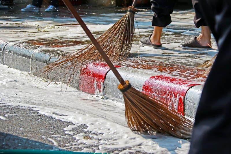Zamyka w górę miotła pracownika czyści brudnego footpath fotografia royalty free