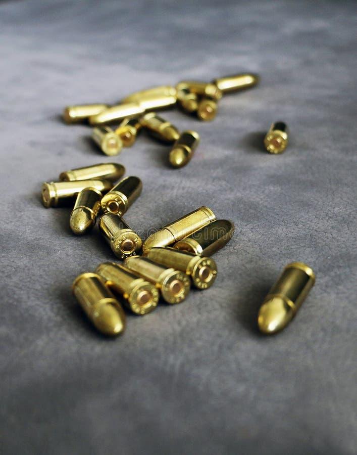 Zamyka w górę 9 mm złotego pistoletowego pociska ammo na tle obrazy stock