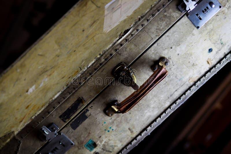 Zamyka w górę odosobnionej starej używać walizki z nitami, rzemiennym chwytem i kombinacja kędziorkami, zdjęcie royalty free