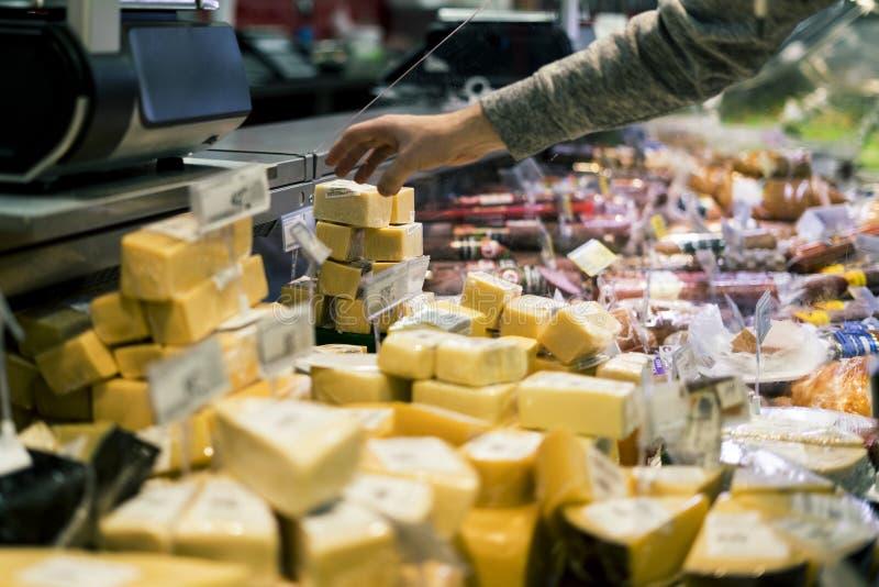 Zamyka w górę osoby ręki kupienia sera w sklepie zdjęcia stock