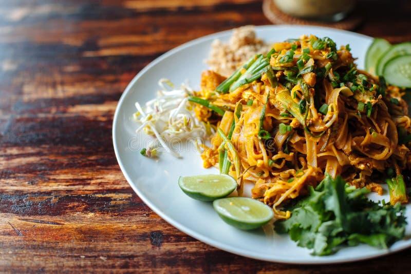 Zamyka w górę Padthai kluski z dymnym tofu i mieszanym warzywem - pszeniczni zarazki, wapno, ogórek, pietruszka na drewnianym tex zdjęcia stock