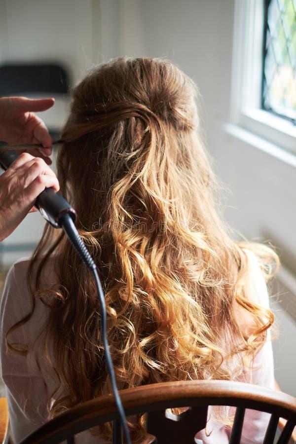 Zamyka w górę panny młodej ślubnego uczesania z elektrycznym włosianym curler na zdjęcia stock