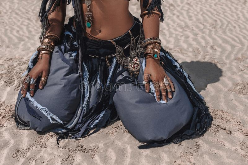 Zamyka w górę pięknego młodego eleganckiego plemiennego tancerza w orientalnym kostiumowym obsiadaniu na piasku outdoors fotografia royalty free