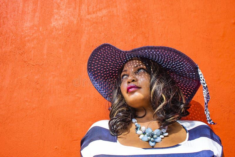 Zamyka w górę pięknej Afrykańskiej kobiety w błękitnej i białej pasiastej smokingowej modelacji przed tradycyjnym domem z pomarań fotografia stock