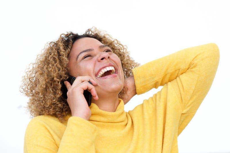 Zamyka w górę pięknej amerykanin afrykańskiego pochodzenia kobiety opowiada na telefonie komórkowym i śmia się przeciw odo fotografia royalty free