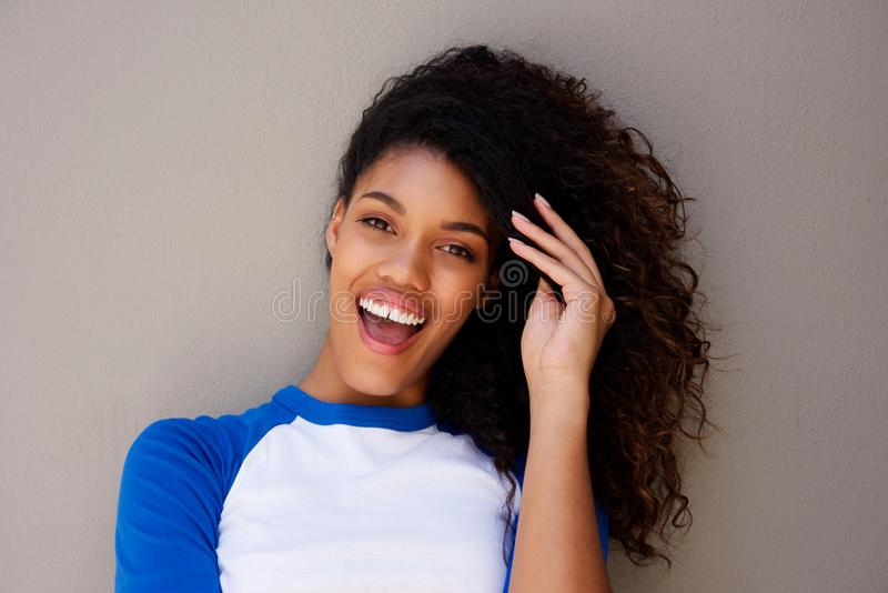 Zamyka w górę pięknej młodej amerykanin afrykańskiego pochodzenia kobiety ono uśmiecha się z ręką w włosy przeciw szarości ściani obraz royalty free