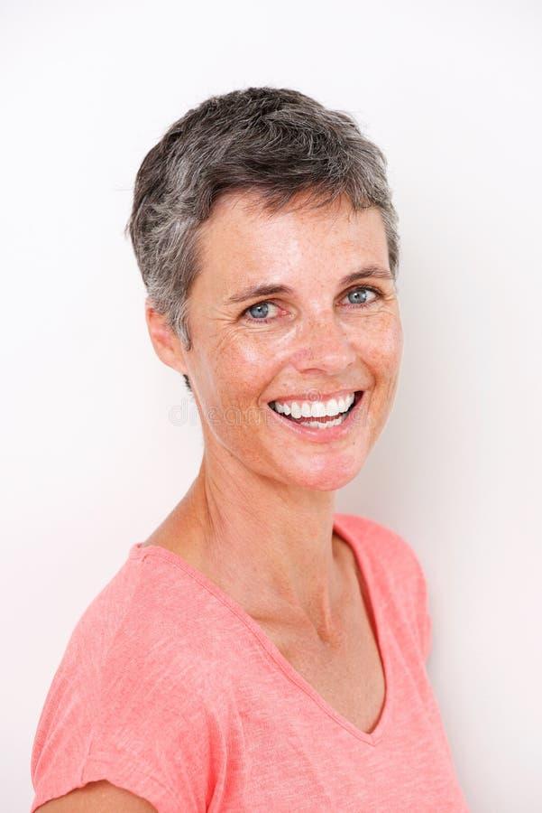 Zamyka w górę pięknej wiek średni kobiety ono uśmiecha się biel ścianą zdjęcia royalty free