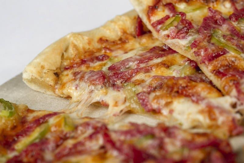 Zamyka w górę pizzy na drewnianej desce na białym tle obraz royalty free