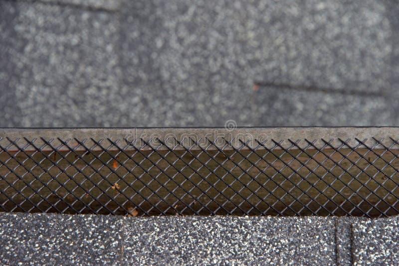 Zamyka w górę podeszczowej rynny zakrywającej z siatka liścia strażnikiem na zdjęcia royalty free