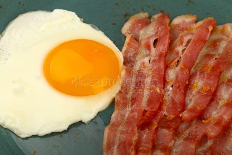 Zamyka w górę pogodnego bocznego jajka i bekonu na błękita talerzu obraz stock