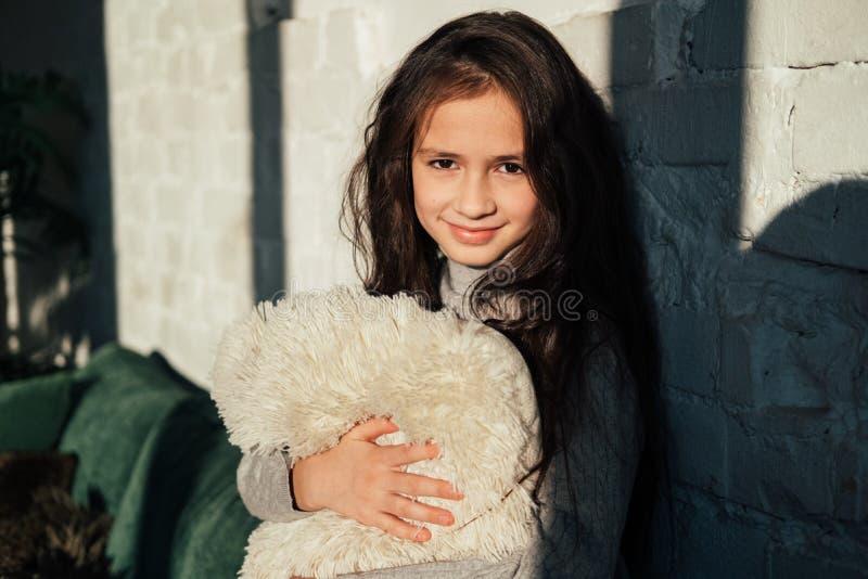 Zamyka w górę Portreta śliczna mała dziewczynka Uśmiechnięty caucasian dzieciak patrzeje kamerę z poduszką w ona ręki Wygodny dom obraz stock