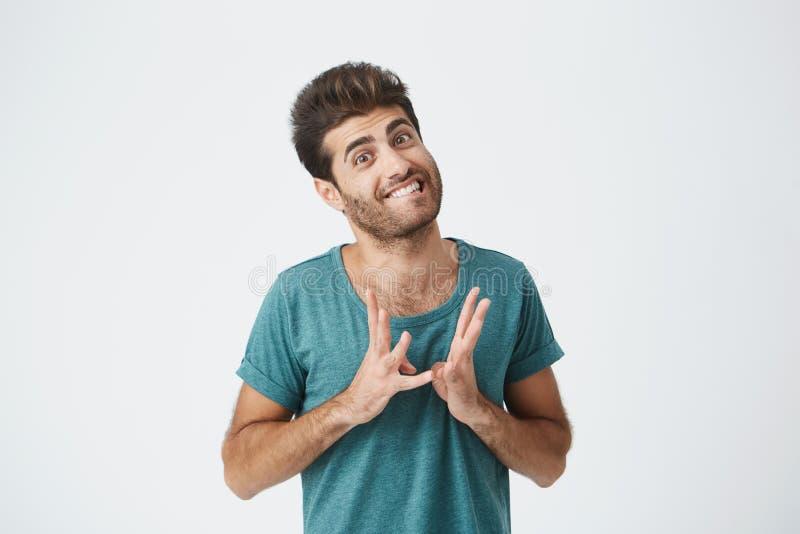 Zamyka w górę portreta śmieszny elegancki hiszpański facet w błękitnym tshirt, zjadliwych wargach i gestykulować z ręk wyrażać, zdjęcia stock
