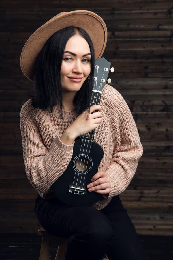 Zamyka w górę portreta atrakcyjna brunetki kobieta jest ubranym sweather i kapelusz z piękną gitarą Drewniany tło obrazy stock