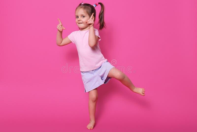 Zamyka w górę portreta berbecia dziecka dziewczynki pozycja w różowej przypadkowej t koszula, purpurach krótko i, wskazuje pierws zdjęcie royalty free