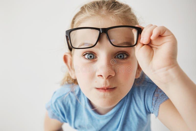 Zamyka w górę portreta ciekawa mała dziewczynka z duży niebieskich oczu stać zamknięty i patrzeć w kamerze, trzyma szkła z obrazy stock