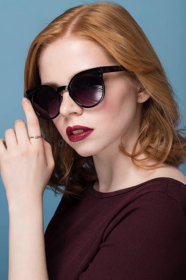 Zamyka w górę portreta elegancka młoda kobieta w okularach przeciwsłonecznych przeciw błękitnemu tłu fotografia stock