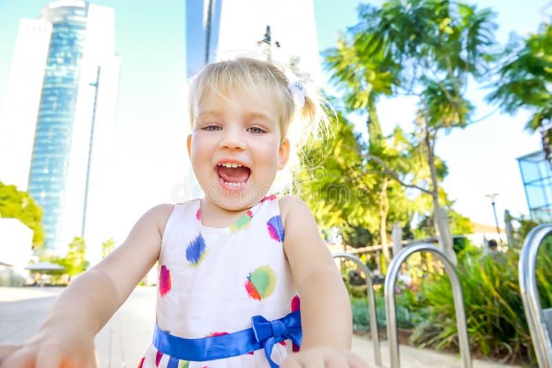 Zamyka w górę portreta emocjonalna śliczna mała blondy berbeć dziewczyna w sukni w miasto parku z nowożytnymi drapaczy chmur budy zdjęcie royalty free