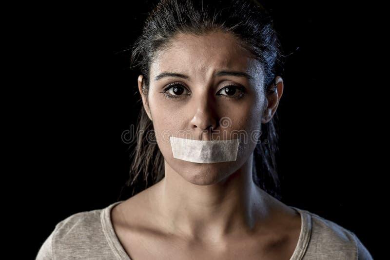 Zamyka w górę portreta młoda atrakcyjna kobieta z usta i wargami pieczętującymi w adhezyjnej taśmie krępującej fotografia royalty free