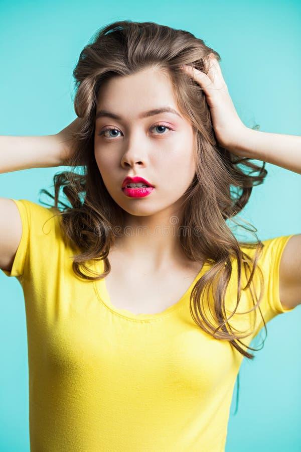 Zamyka w górę portreta młoda piękna brunetki kobieta patrzeje kamerę i dźwignięcia włosy zdjęcia stock