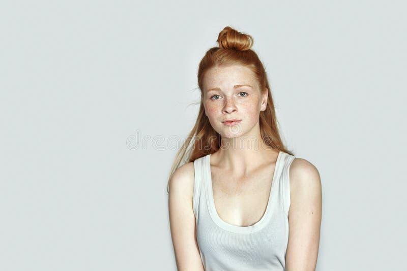 Zamyka w górę portreta młoda piękna rudzielec beginner modela kobieta w białej koszulki ćwiczy pozować pokazywać emocje na biały  fotografia royalty free