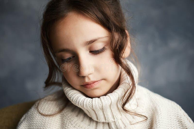 Zamyka w górę portreta młoda piękna zadumana dziewczyna w białej koszulowej patrzeje kamerze obrazy royalty free