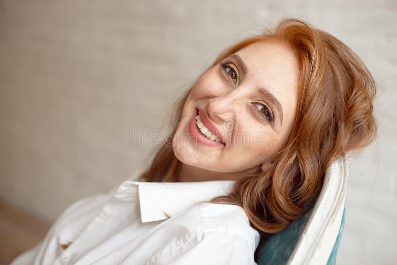 Zamyka w górę portreta młoda uśmiechnięta miedzianowłosa kobieta na czarnym tle zdjęcia stock