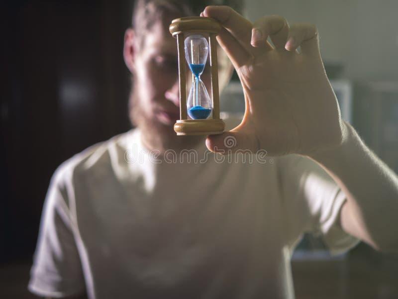 Zamyka w górę portreta młodego brodatego mężczyzna mienia studenckiego hourglass, czasu pojęcie obrazy stock
