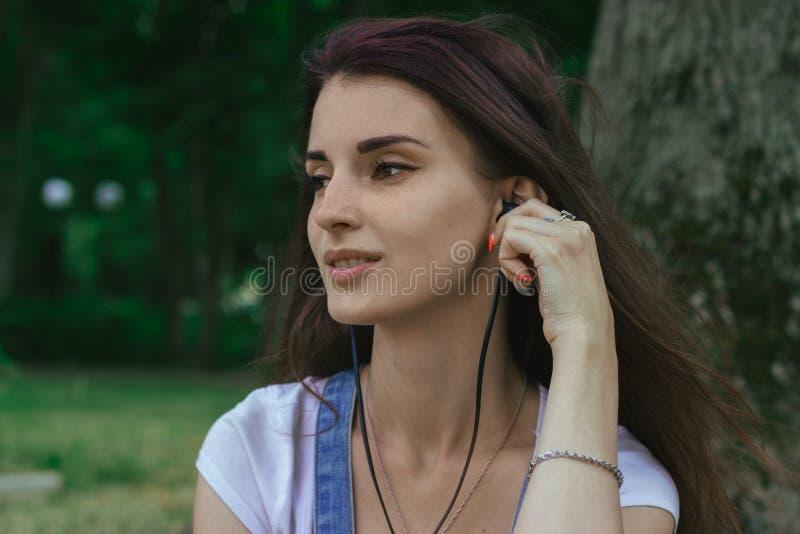 Zamyka w górę portreta młodej brunetki dziewczyny słuchająca muzyka z hełmofonami fotografia royalty free